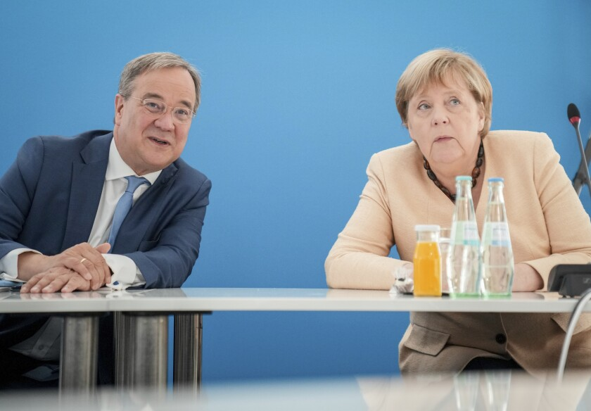Armin Laschet, left, candidate for Chancellor of Germany's center-right block and Christian Democratic Union chairman talks with Chancellor Angela Merkel during a CDU party's executive meeting in Berlin, Germany, Monday, Sept. 13, 2021. (Kay Nietfeld/dpa via AP)