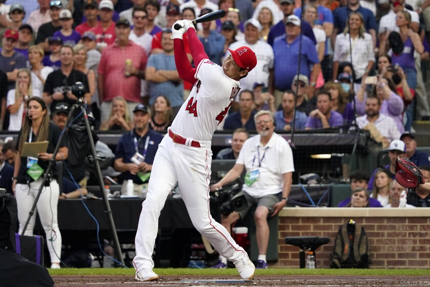 A baseball player in a white and red uniform swings his bat. A crowd is in the stands in the background.