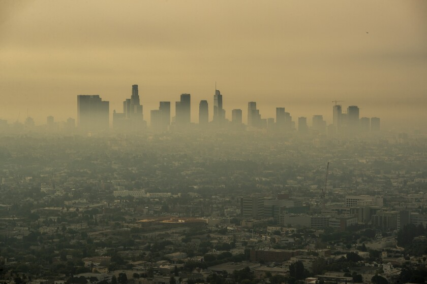Smoke from Southern California wildfires drifts through the L.A. Basin, obscuring downtown skyscrapers in the distance.
