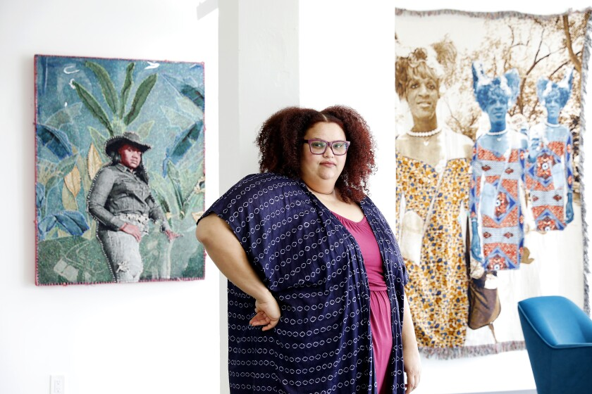 April Bey stands wears a dotted blue robe and stands with her hand on her hip before works in her studio.