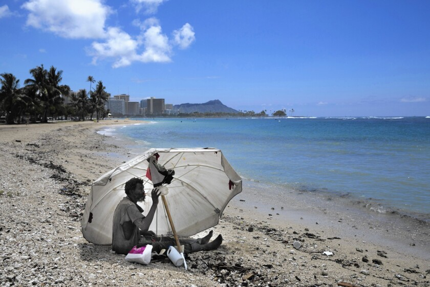 A homeless man sits on the beach at Ala Moana Beach Park in Honolulu. Hawaii now has the nation's highest rate of homeless people per capita.
