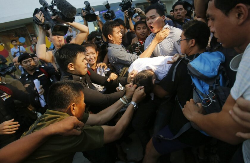 Police officers drag student protesters in Bangkok, Thailand Friday, May 22, 2015. Thai police detained anti-coup protestors who attempted to organize activity marking the first anniversary of the military coup. (AP Photo/Sakchai Lalit)