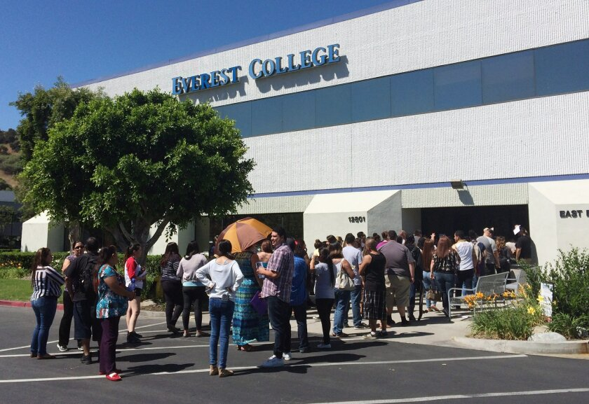 Students wait outside Everest College, Tuesday, April, 28, 2015 in Industry, Calif., hoping to get their transcriptions and information on loan forgiveness and transferring credits to other schools. Corinthian Colleges shut down all of its remaining 28 ground campuses on Monday, April 27, displacin