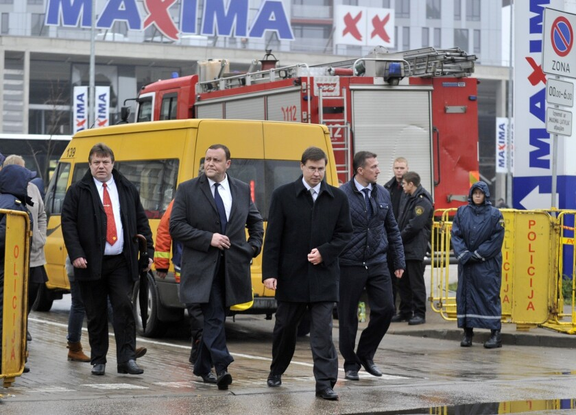 Latvian Prime Minister Valdis Dombrovskis, front center, visits a collapsed supermarket in the capital, Riga, last week.