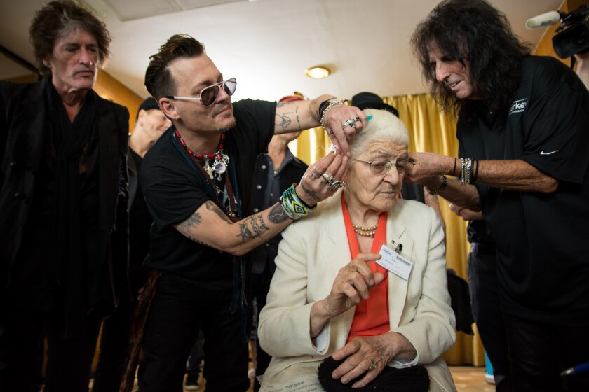 In Lisbon on Friday, Johnny Depp, second from left, and Alice Cooper install hearing aids on a patient of the Starkey Hearing Foundation. Joe Perry, left, watches.