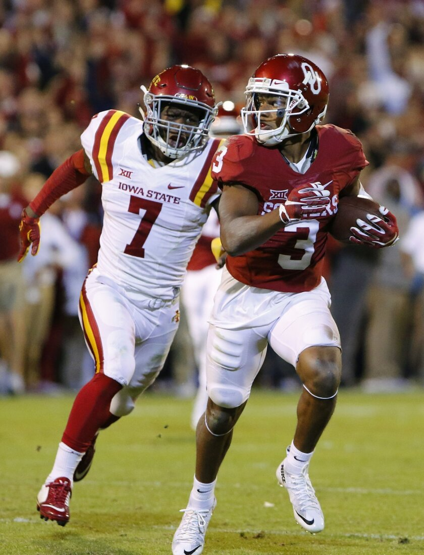 Oklahoma wide receiver Sterling Shepard (3) runs the ball in for a touchdown ahead of Iowa State defensive end Seth Nerness (7) during the fourth quarter of an NCAA college football game in Norman, Okla., on Saturday, Nov. 7, 2015. Oklahoma won 52-16. (AP Photo/Alonzo Adams)