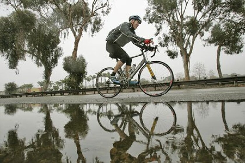 Tedd Benson, 60, rode in light rain yesterday on North Coast  Highway 101 in Leucadia. He lives in New Hampshire and is  staying in Encinitas for a visit.  (Charlie Neuman / Union-Tribune)