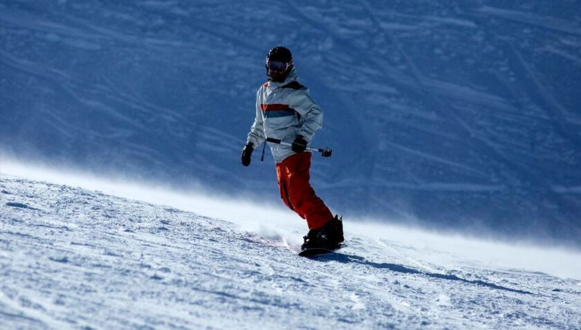 A snowboarder carves down a run at Mammoth Mountain. The deal under which a Colorado partnership acquired Mammoth Resorts was completed Monday.
