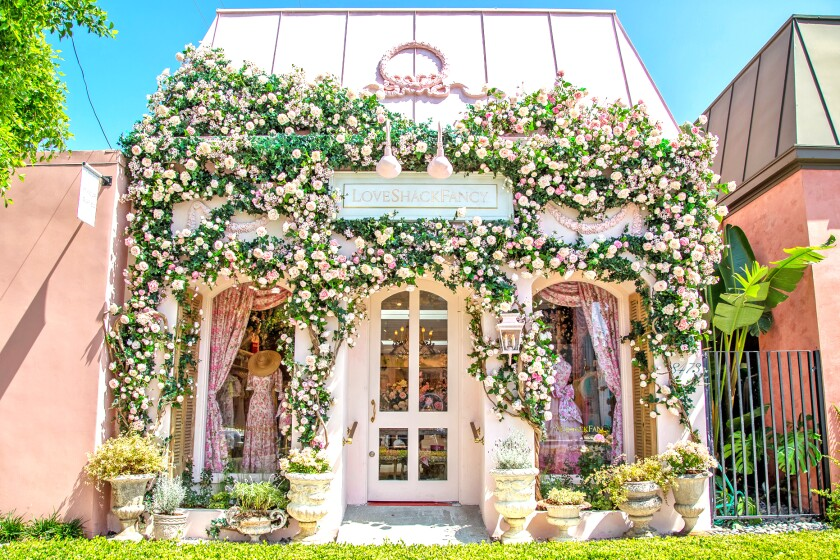 The entrance of LoveShackFancy's Melrose Place flagship, a rose-covered-cottage.