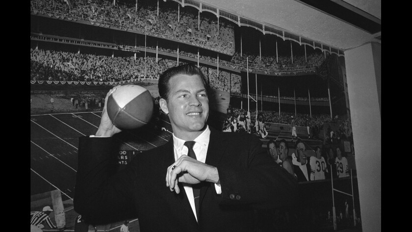 Halfback Frank Gifford cocks his passing arm as he stands in front of a photo mural of the Polo Grounds at the offices of the New York Giants in New York's Coliseum on April 2, 1962.
