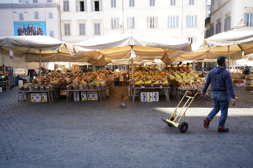 A man pulls a trolley at an emtpy Campo dei Fiori open-air market, in Rome, Tuesday, March 10, 2020. The Italian government is assuring its citizens that supermarkets will remain open and stocked after panic buying erupted after broad anti-virus measures were announced nationwide, sparking overnight runs on 24-hour markets. (AP Photo/Andrew Medichini)