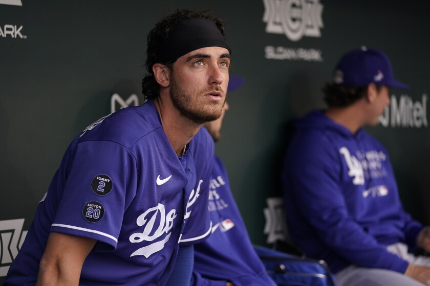 Dodgers center fielder Cody Bellinger sits in the dugout before a spring training baseball game against the Chicago Cubs.