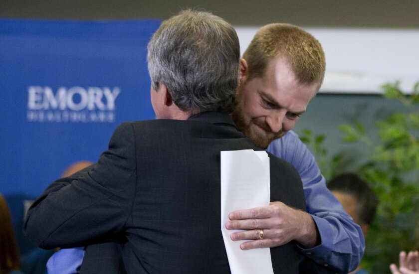 Ebola victim Dr. Kent Brantly, right, hugs a member of the medical staff that treated him, after being released from Emory University Hospital Thursday, Aug. 21, 2014, in Atlanta. Another American aid worker, Nancy Writebol, who was also infected with the Ebola virus, was released from the hospital