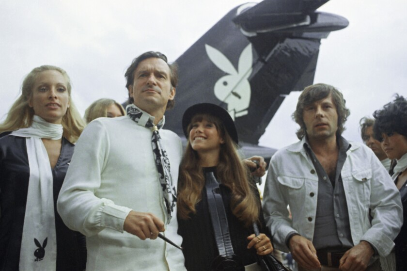 Playboy publisher Hugh Hefner, second from left, arrives in Paris in 1970 with his girlfriend Barbi Benton, center, and film director Roman Polanski.