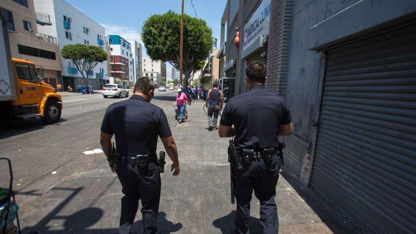 LOS ANGELES, CA - JULY 15: Officers Richard Torres, right, and Gerado Montano, left, walk around sk