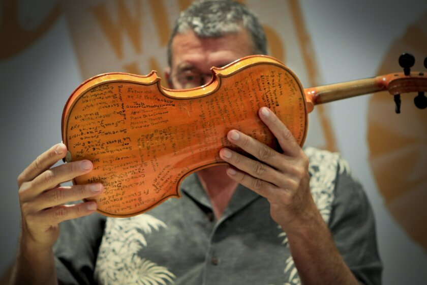 Military antiques expert Larry Stone examines a violin from a World War I Army Colonel, with his diary etched on the back, brought in by Wayne and Sharron Myers, to the appraisal event held at the BlueVault San Diego.
