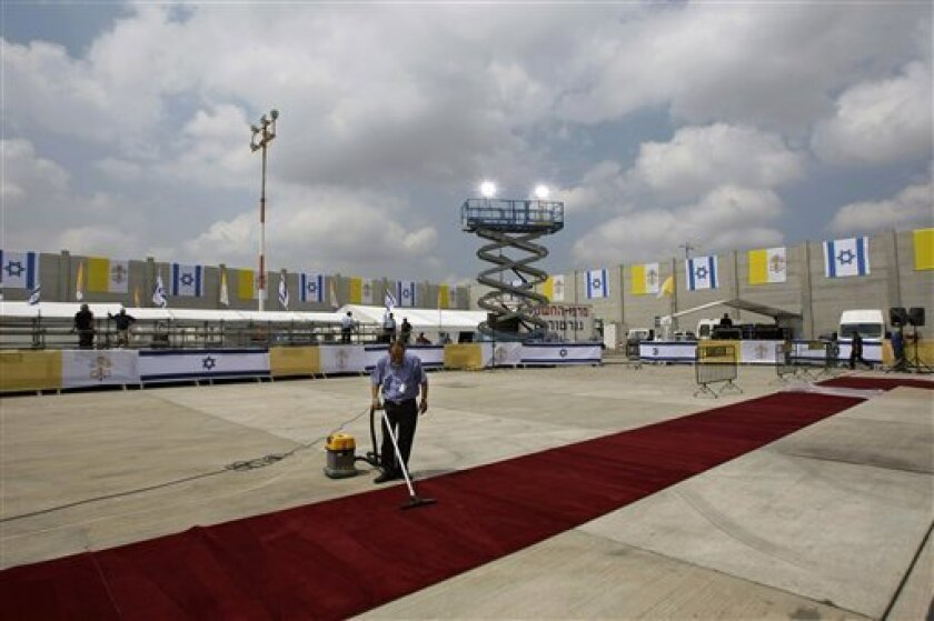 An Israeli airport worker cleans the red carpet a day before the arrival of Pope Benedict XVI at Ben Gurion airport near Tel Aviv, Israel, Sunday, May 10, 2009. Pope Benedict XVI on Sunday urged Middle East Christians to persevere in their faith despite hardships threatening the existence of their ancient communities. Pope Benedict XVI is on a week long tour in the Middle East that includes Jordan, Israel, and the Palestinian territories. (AP Photo/Ariel Schalit)