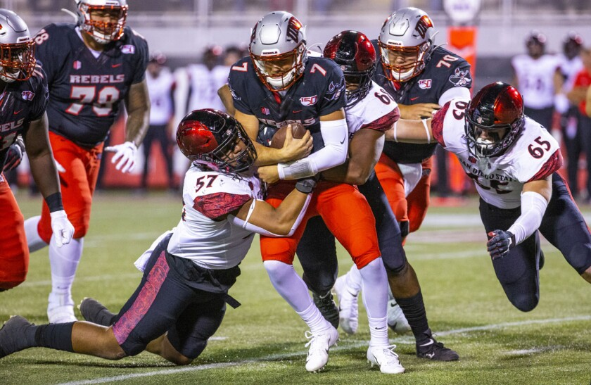 San Diego State defensive linemen sack UNLV quarterback Kenyon Oblad during last year's game at Sam Boyd Stadium.
