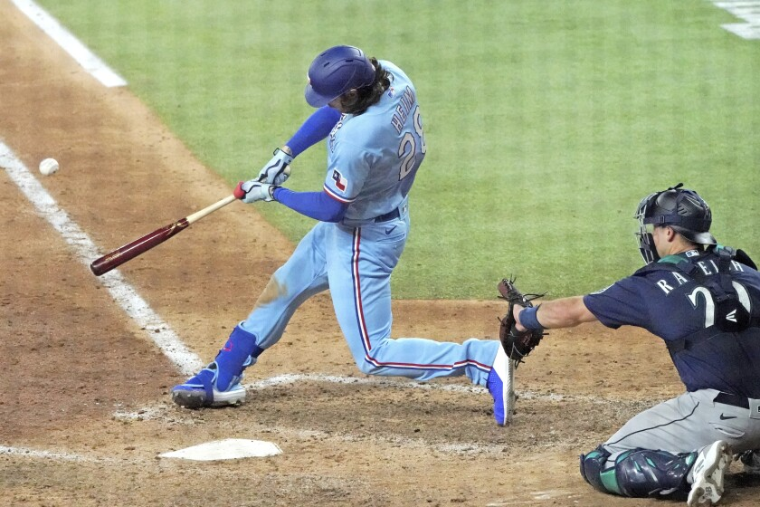 El bateador designado Jonah Heim, de los Rangers de Texas, conecta el jonrón de la victoria en la parte baja de la novena entrada del partido contra los Marineros de Seattle en Arlington, Texas, el domingo 1 de agosto de 2021. (AP Foto/Louis DeLuca)