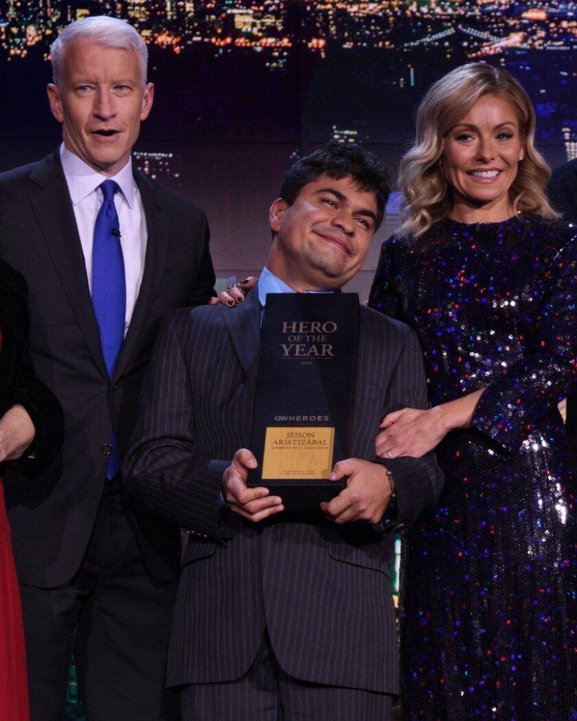 El periodista Anderson Cooper y la presentadora Kelly Ripa le entregan el reconocimiento a Jeison Aristizábal. Foto de las redes sociales de CNN-Heroes