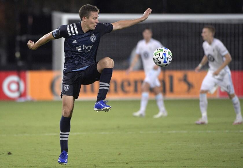 Sporting Kansas City defender Matt Besler, left, controls a pass during the first half of the team's MLS soccer match against Minnesota United, Sunday, July 12, 2020, in Kissimmee, Fla. (AP Photo/Phelan M. Ebenhack)