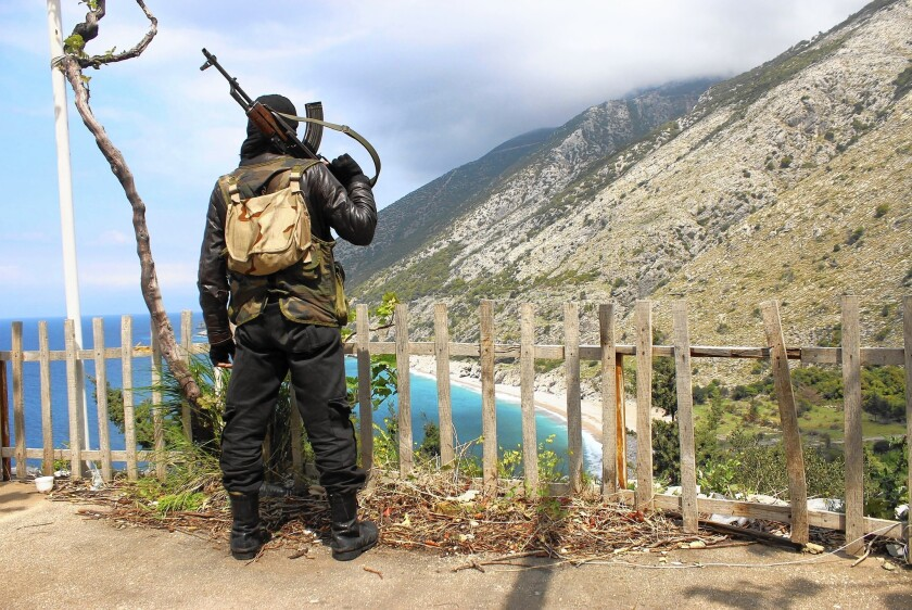 Syrian rebel fighter looks out from ridge
