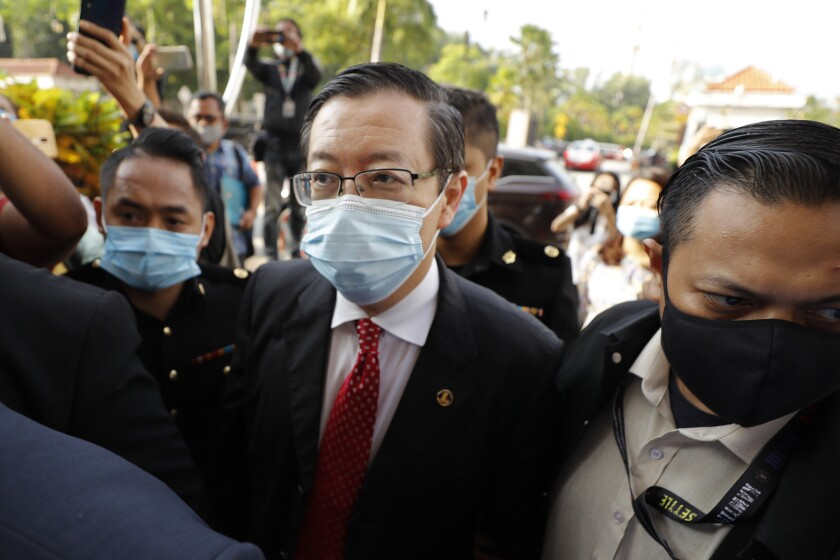 Former Finance Minister and Penang chief minister Lim Guan Eng, center, is escorted by Anti Corruption officers as he arrives at courthouse in Kuala Lumpur, Malaysia, Friday, Aug. 7, 2020. Lim was arrested last night to be charged with corruption in connection with the Penang undersea tunnel project, the Malaysian Anti-Corruption Commission (MACC). (AP Photo/Vincent Thian)