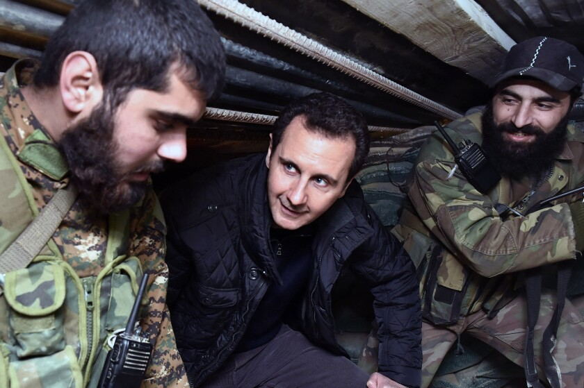 Syrian President Bashar Assad, center, speaks with Syrian troops during his visit to the front line in the eastern Damascus district of Jobar, Syria.