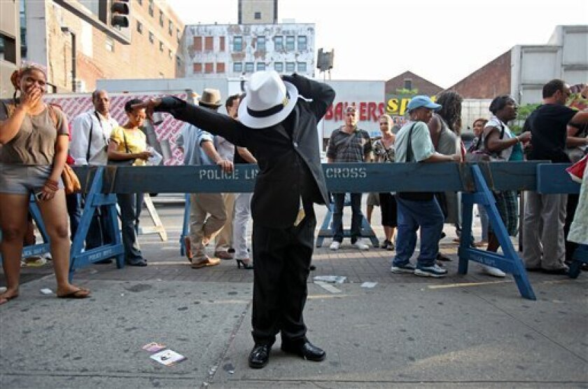 Antonio Williams, 7, of Orlando Fla., performs the dance moves of Michael Jackson for those waiting online for the doors to open for amateur night, which is dedicated to the late singer, at the Apollo Theater in the Harlem neighborhood of New York Wednesday, July 1, 2009. (AP Photos/David Goldman)