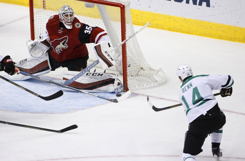 Dallas Stars' Jamie Benn (14) sends the puck at Arizona Coyotes' Louis Domingue (35) before it slips past the goalie for a score during the second period of an NHL hockey game Thursday, Feb. 18, 2016, in Glendale, Ariz. (AP Photo/Ross D. Franklin)