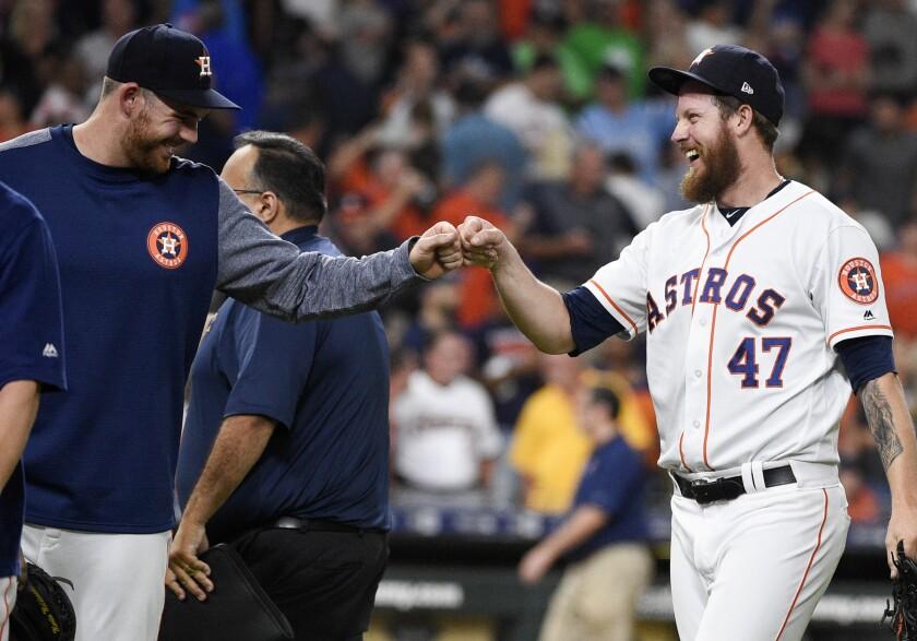 Houston Astros relief pitcher Chris Devenski, right, celebrates with Joe Biagini.