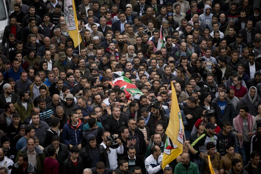 Palestinian mourners carry the body of Ibrahim Skafi, 22, during his funeral in the West Bank city of Hebron, Thursday, Nov. 5, 2015. Skafi rammed his vehicle into an Israeli police officer in the West Bank on Wednesday, seriously injuring him before he was shot and killed, police said. (AP Photo/M