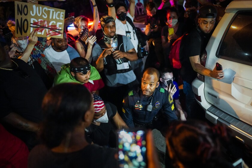 A Dallas police officer talks with protestors on June 2.