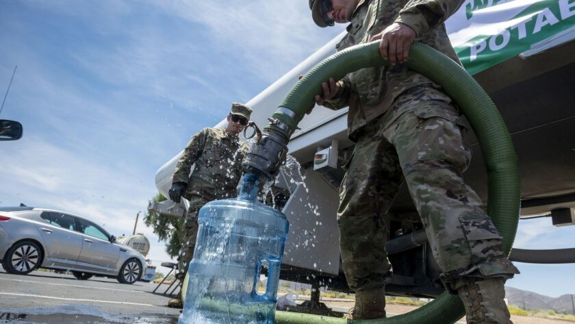 Soldiers fill a water container
