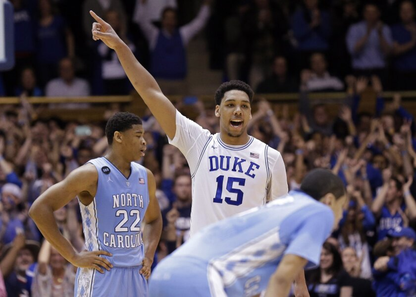 Duke's Jahlil Okafor (15) reacts as North Carolina's Isaiah Hicks (22) looks away late in the second half of an NCAA college basketball game in Durham, N.C., Wednesday, Feb. 18, 2015. Duke won 92-90 in overtime. (AP Photo/Gerry Broome)