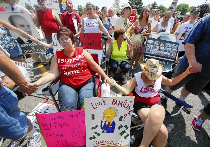Protesters pray before a rally outside a Market Basket store in Tewksbury, Mass., on Aug. 5.