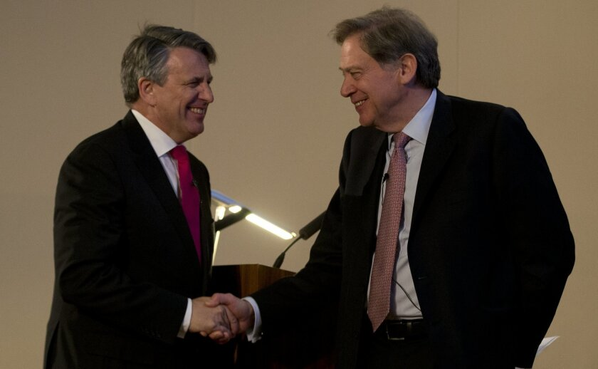 Ben van Beurden, CEO of Royal Dutch Shell, left, shakes hands with the Chairman GB group Andrew Gould during a press conference to announce Royal Dutch Shell has agreed to buy British Gas, in London, Wednesday, April 8, 2015. Royal Dutch Shell has agreed to buy British gas producer BG Group for 47