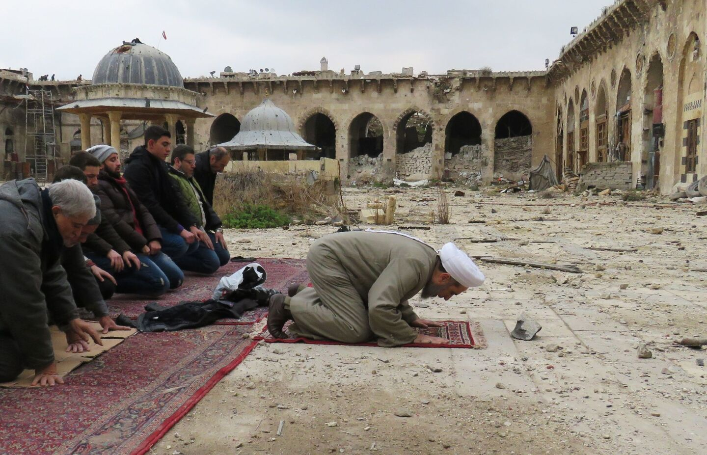Syrians pray in the ancient Umayyad mosque in the old city of Aleppo, as civilians are allowed access to some neighbourhoods recently retaken by Syrian government forces.