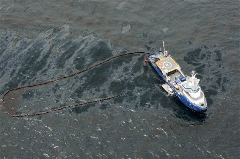 In this aerial photo taken in the Gulf of Mexico more than 50 miles southeast of Venice on Louisiana's tip, a boat with an oil boom tries to contain oil spilled from the explosion and collapse of the Deepwater Horizon oil rig, approximately seven miles from where the rig sunk, on Friday, April 23, 2010. (AP Photo/Gerald Herbert)