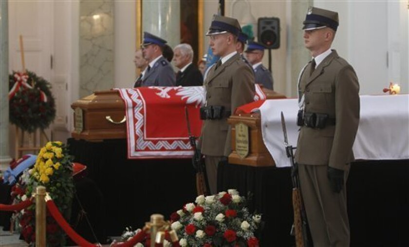 Soldiers flank the coffins of the presidential couple lying in state on Friday, April 16, 2010 in the Presidential Palace in Warsaw, Poland.  Polish President Lech Kaczynski who was killed in a plane crash in Russia is going to be buried in Krakow on Sunday.   (AP Photo/Czarek Sokolowski)