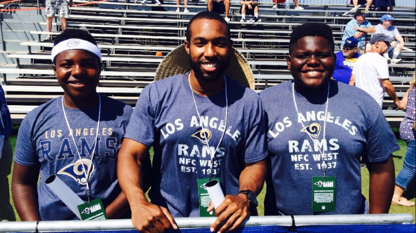 Ian Thompson is flanked by his nephews Jacob Sanders, left, and Joshua Sanders, right, during a recent Rams practice.