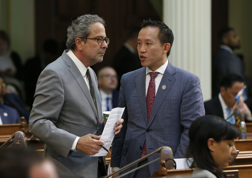 In this Wednesday May 29, 2019 photo, Democratic Assemblymen Richard Bloom, of Santa Monica, left, and David Chiu, of San Francisco, talk during the Assembly session in Sacramento, Calif. The Assembly approved a a bill capping rent increases by Chiu, co-authored by Bloom, Wednesday and sent it to the Senate. (AP Photo/Rich Pedroncelli)