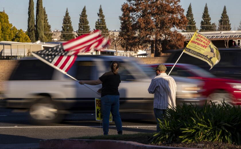 """Two people wave an American flag and a """"Recall Gavin Newsom"""" flag on the side a road."""