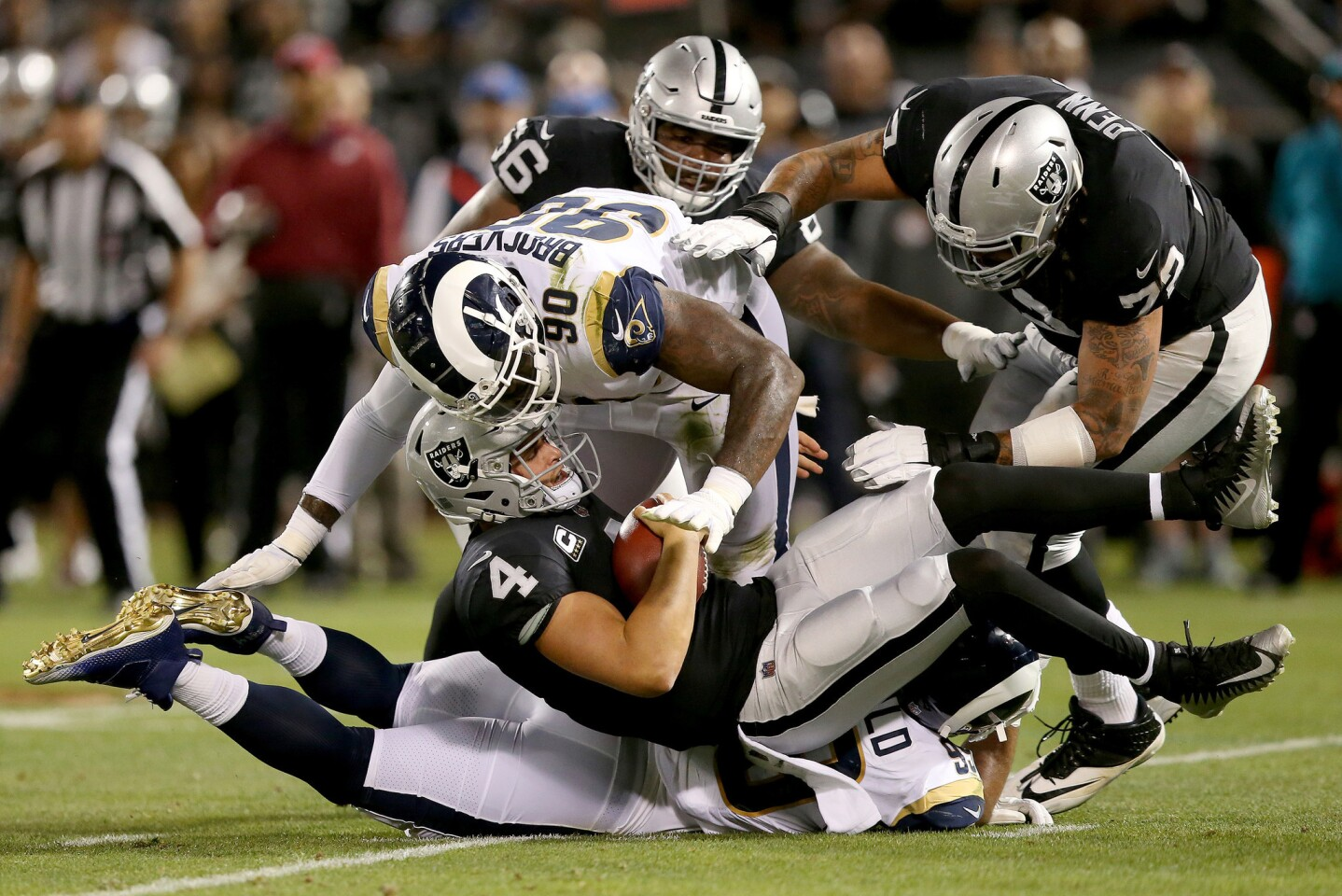 Oakland Raiders quarterback Derek Carr (4) is sacked by Los Angeles Rams defensive tackle Michael Brockers (90) and a defensive penalty is called in the first quarter of their NFL game at the Coliseum in Oakland, Calif., on Monday, Sept. 10, 2018. (Jane Tyska/Bay Area News Group/TNS) ** OUTS - ELSENT, FPG, TCN - OUTS **