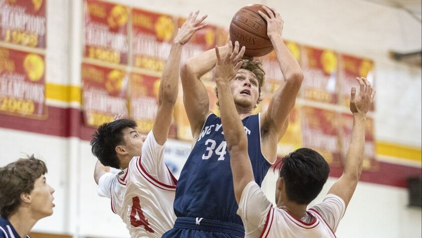Newport Harbor's Dayne Chalmers goes up for a shot against Loara's Tyler Nanthavong, left, and David