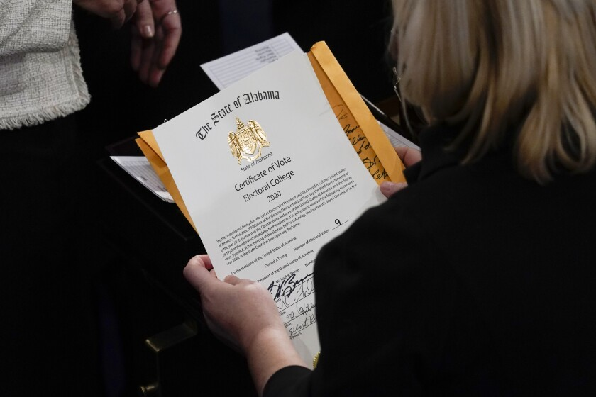 The gold-embossed certification of electoral college votes for the state of Alabama is unsealed in Congress Jan. 6.