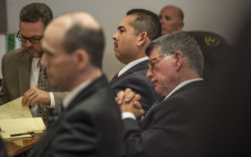 Former Fullerton police officer Manuel Ramos, center,  listens to the opening statement during his trial on Monday, Dec. 2, 2013 in Santa Ana, Calif.  Orange County District Attorney Tony Rackauckas told jurors that former Fullerton officers Ramos and Jay Cicinelli were responsible for the death of