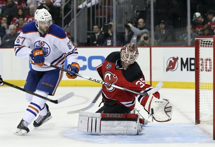 New Jersey Devils goalie Cory Schneider (35) makes a glove save on a shot by Edmonton Oilers left wing Benoit Pouliot (67) during the first period of an NHL hockey game Tuesday, Feb. 9, 2016, in Newark, N.J.  (AP Photo/Mel Evans)