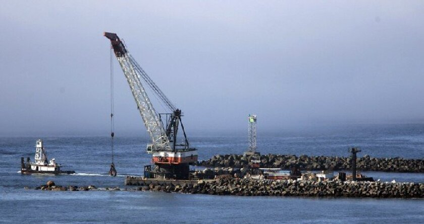 A crane moved boulders last November on the south jetty of the Mission Bay channel. Federal stimulus funds were used to restore the jetty, which was battered by storms over the years and become a boating hazard.
