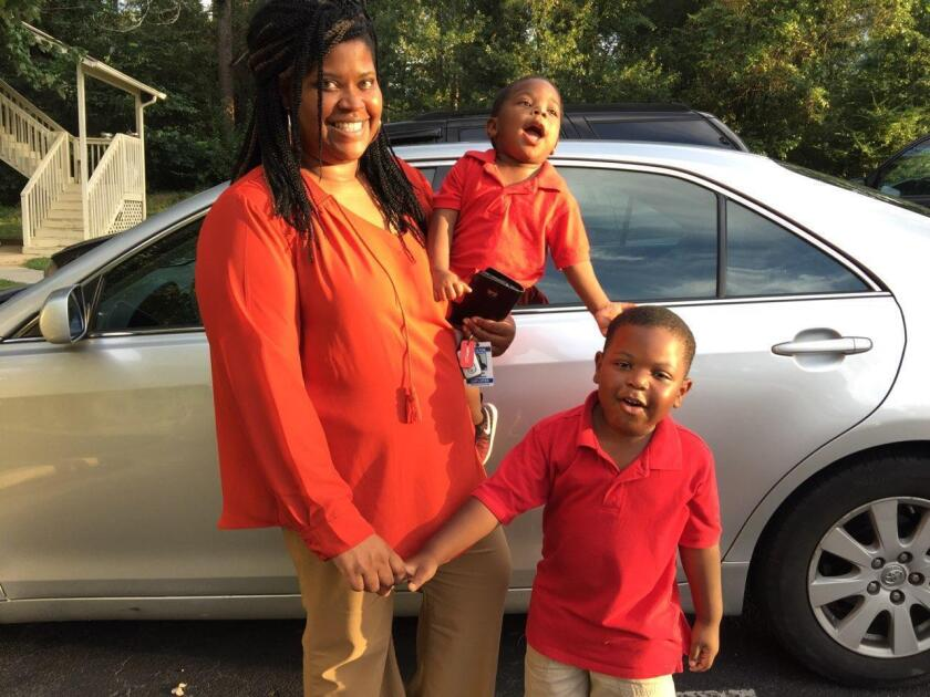 In this 2017 photo provided by her family, Saferia Johnson, of Thomasville, Ga., holds her sons, Kyrei, center, and Josiah. Johnson earned a reputation as a mentor and mother figure to many and time and again, she was a fast friend, who followed a chance encounter with an outflow of kindness that ensured would-be strangers instead lived lives forever intertwined. In August 2020, she died at the age of 36 from COVID-19. (Family photo via AP)